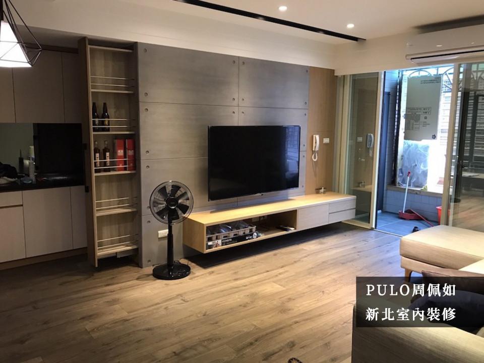 客廳以清水模為重點,搭配暖色的光線營造出整體的工業風格,主牆後的空間也另外設計收納拉櫃,發揮更多的空間效益。進門的落地窗選用全透明的玻璃拉門,在增加客廳採光的同時,另外在訪客到來時更能一目了然。-PULO裝潢平台