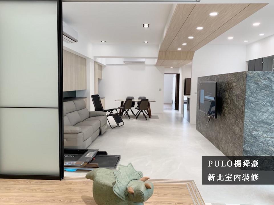 電視牆面不採頂天的設計,用以保留後方隔間的採光及空間感,並在色調上挑選強烈的暗色系,點出客廳重點。天花板以木作增加視覺效果,也與沙發後方的櫃體形成一致的色彩效果,空間也不擺放過多家具,保持通道間的流暢。-PULO裝潢平台